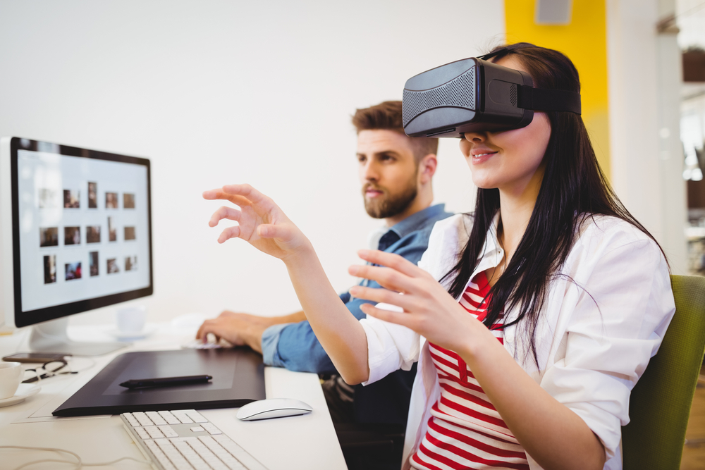 Young female executive enjoying augmented reality headset at creative office